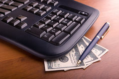Keyboard and money. The computer keyboard and the dollars lying under it Royalty Free Stock Images