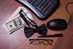 Keyboard and mouse, glasses, black bowtie black pen, note book page and money. A place for records, business plan, money background, hundred dollar bills front royalty free stock photography