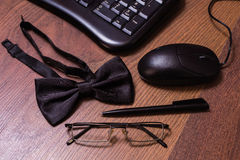 Keyboard and mouse, glasses, black bowtie black pen. Note book page and money, a place for records, business plan, money background, hundred dollar bills front royalty free stock photography