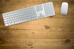 Keyboard and mouse on a wooden table top. Keyboard and mouse on a wooden table stock photos
