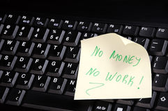 Keyboard with 'no money -no work. Sticky note on a laptop keyboard with 'no money -no work' on it Royalty Free Stock Images