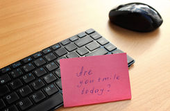 Keyboard with a note on the wooden desk. Stock Photos