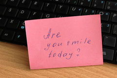 Keyboard with a note on the wooden desk. Royalty Free Stock Photo
