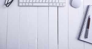 Keyboard notebook pen on wooden background stock photography