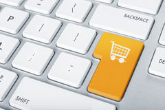 Keyboard online shopping. Online shopping cart proceed keyboard concept orange button white icon Stock Photos