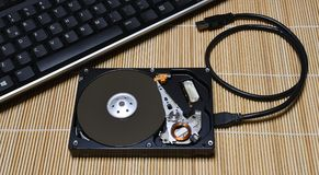 Keyboard and Open Hard Disk Drive on wood background Stock Image