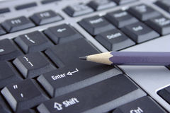 The keyboard and pencil. The pencil lying on a key Enter the computer keyboard Stock Photo