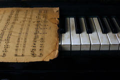 Keyboard of the piano and old notes Stock Photo