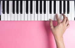 Keyboard player hand is playing on keyboard with pink Stock Photos