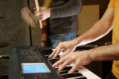 Keyboard player in studio. guitarist out of focus Royalty Free Stock Image