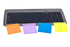 Keyboard with postit. Grey keyboard with postit stickers on it, different colors Royalty Free Stock Photo