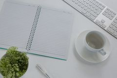 Keyboard, pot plant, pen, book, coffee cup and saucer on table. Overhead of keyboard, pot plant, pen, book, coffee cup and saucer on table Royalty Free Stock Photography