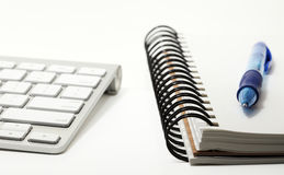 Keyboard and sketchbook with pen. Wireless computer keyboard and sketchbook or notepad concept, with a ballpoint pen Royalty Free Stock Photography