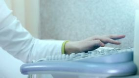 Keyboard ultrasound device. Close up, doctor`s hand presses buttons and scanning male patient.  stock footage