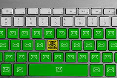 Keyboard with yellow email virus button surrounded with green email buttons Royalty Free Stock Images