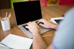 Keyboarding бизнесмена на портативном компьютере с пустым экраном с космосом экземпляра стоковые фотографии rf