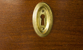 Keyhole. Closeup of a golden keyhole on wood background Stock Photography