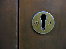 KEYHOLE. Metal keyhole screwed to a metal door Royalty Free Stock Image