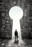 Keyhole. Businessman looking to opened concrete wall in form keyhole Stock Photo