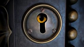 Keyhole. Eyed is peeking through the locked door
