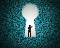 Keyhole on green big data background with businessman standing. Big data privacy and security information technology concept. Rear view of businessman standing stock photo