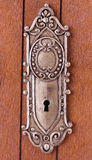 Keyhole with ornament on wooden door Royalty Free Stock Images