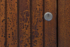 Keyhole on peeling paint texture. Detail of keyhole on old wooden door with peeling paint texture royalty free stock photography