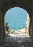 Keyhole To The Med. View through a cannon hole in a medieval wall out to the aqua waters of the Med Royalty Free Stock Photos