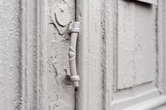 Keyholes конца-вверх с занавесами и ручкой на сером цвете много дверь покрашенная времен треснутая двух-barreled деревянная винта Стоковая Фотография