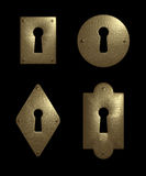Keyholes. A set of four differently shaped, antique looking metal keyholes. Isolated on black background Stock Photos