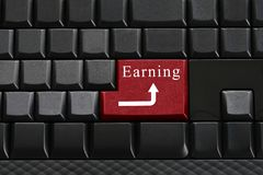 Keypad of black keyboard and have text Earning on enter button. Royalty Free Stock Photos