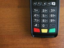 Keypad of  payment terminal standing on the wooden table. Background, copy space stock image