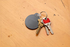 Keyring with blank fob on table. Looking down towards a keyring with assorted keys and round, black blank fob for text Stock Photos