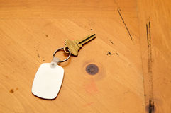 Keyring with key and fob on wood table. A blank white rubber key fob on keyring with a single brass key laying on old wooden table. Copy space on fob and wood Royalty Free Stock Photo