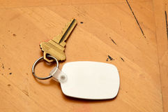 Keyring with key and white fob on wood table. A blank white rubber key fob on keyring with a single brass key laying on old wooden table. Copy space on fob and Stock Photos