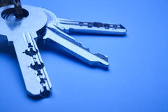 Keyring with keys in blue tone over an empty background. Horizontal Royalty Free Stock Image
