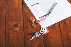 Keyring of small house with contract bank, fountain pen and coins over brown wood. Keyring of small house with red roof with contract bank, fountain pen and Royalty Free Stock Image