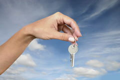 Keys. A woman holding some keys - beautiful sky on the background royalty free stock photography