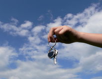 Keys. Hand and keys on blue sky with clouds Royalty Free Stock Images
