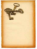 Keys against paper. Sheet of old paper with retro ornamented keys against white background Stock Photo
