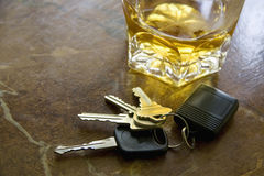 Keys and Alcohol Drink. Close-up of car keys with unfinished alcohol drink on table. Don't drink and drive Royalty Free Stock Images