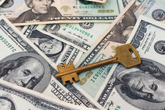 The keys on a background of money. The concept of buying or renting a home. Royalty Free Stock Image