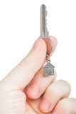 Keys with a charm in a hand. Keys with a charm in the form of the house in a hand on a white background Stock Images