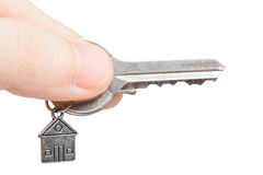 Keys with a charm in a hand. Keys with a charm in the form of the house in a hand on a white background Stock Image