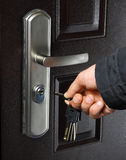 Keys and door. Hand holding keys and try to open the door Royalty Free Stock Photography