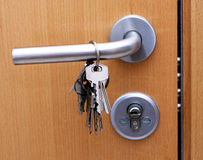 Keys on the door handle. Keys hanging on a door handle of a locked door Stock Photo