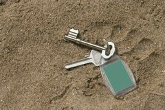 Keys dropped on sand. Key with green fob dropped on sand, in footprint Stock Images