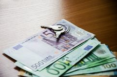 Keys, euro banknotes on the table, close-up. Keys on euro banknotes close-up stock photo