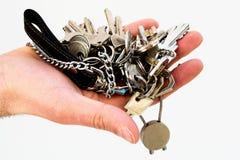 Keys in hand. Hand holding many keys isolated close up Stock Photos