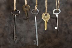 Keys are hanging on the ropes on a brown-gray background. Old keys. Conceptual stock image